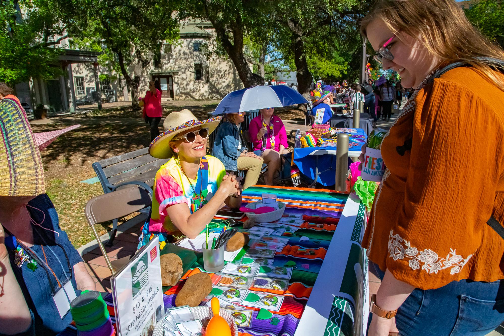 Wendy Black selling Fiesta medals. (Photo by:  Joel Pena  - SA Sentinel Photographer.)