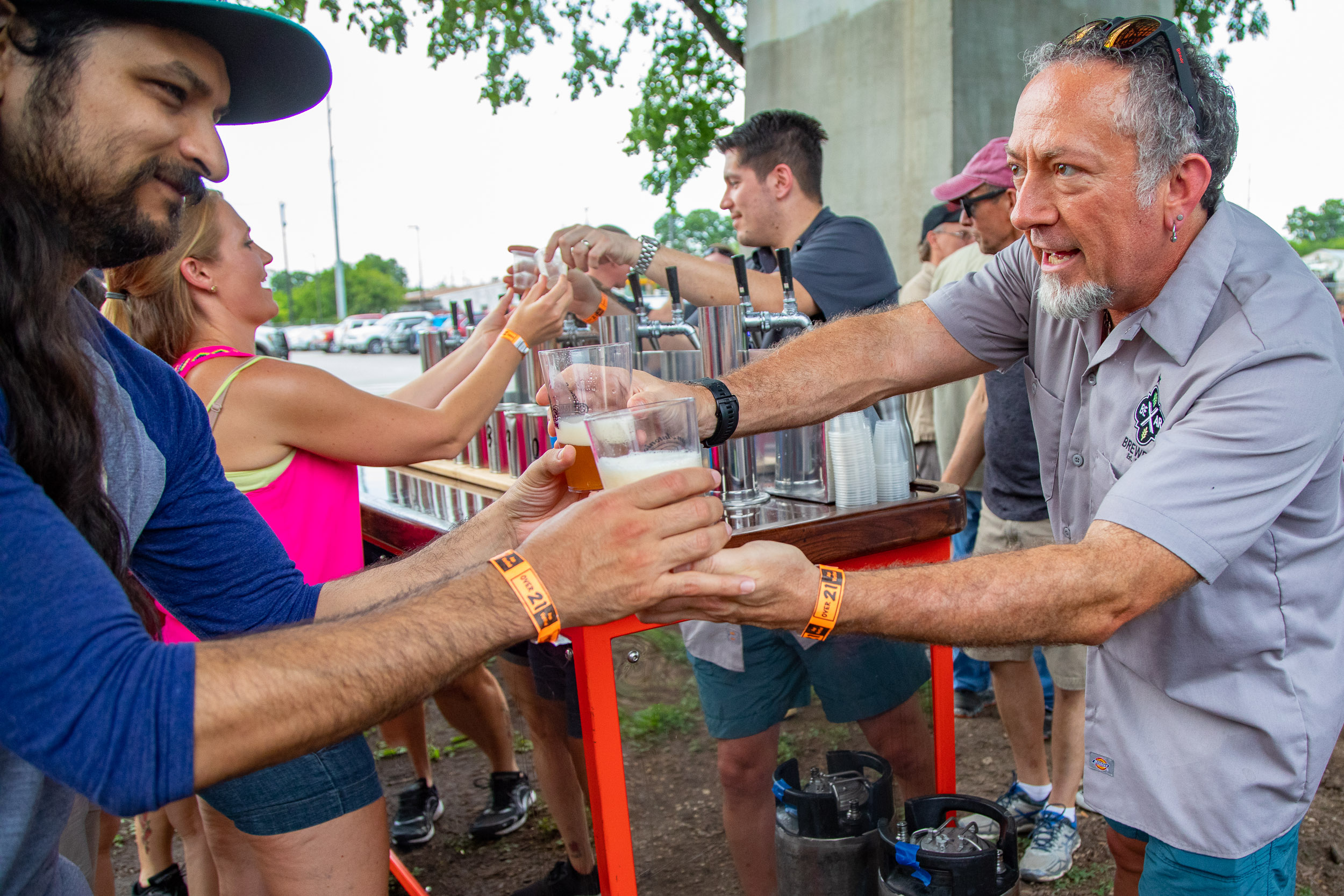 A vendor serves beer to eager patrons. (Photo Credit:  Joel Pena .)