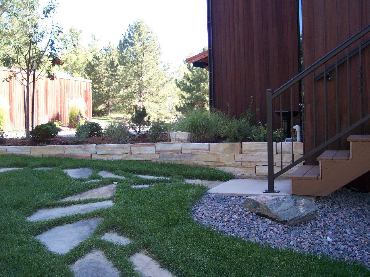 Strip stone wall, flagstone steppers set in grass, and sod install.