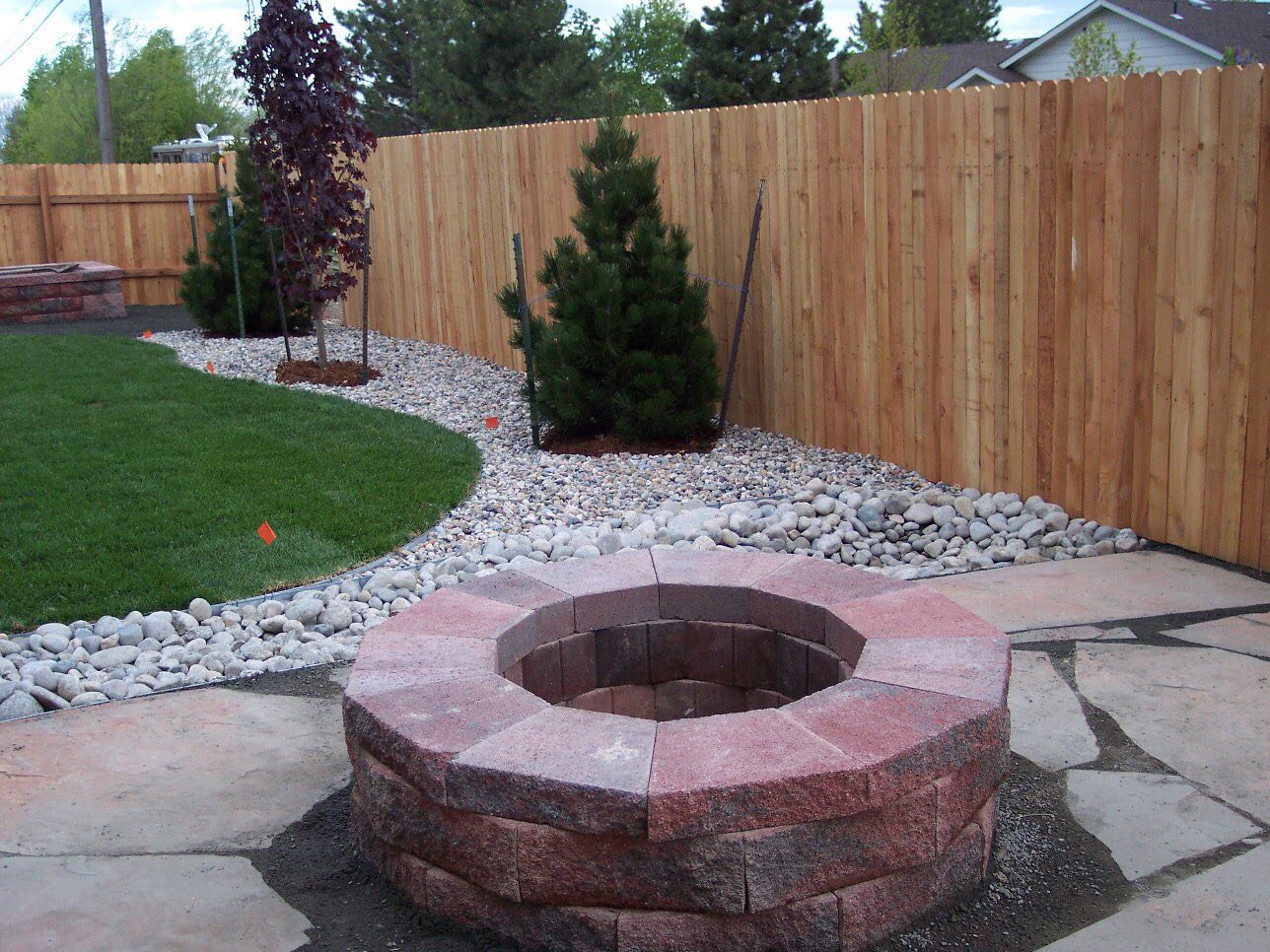 Versa Lok fire pit, fence, plantings, and rock install.