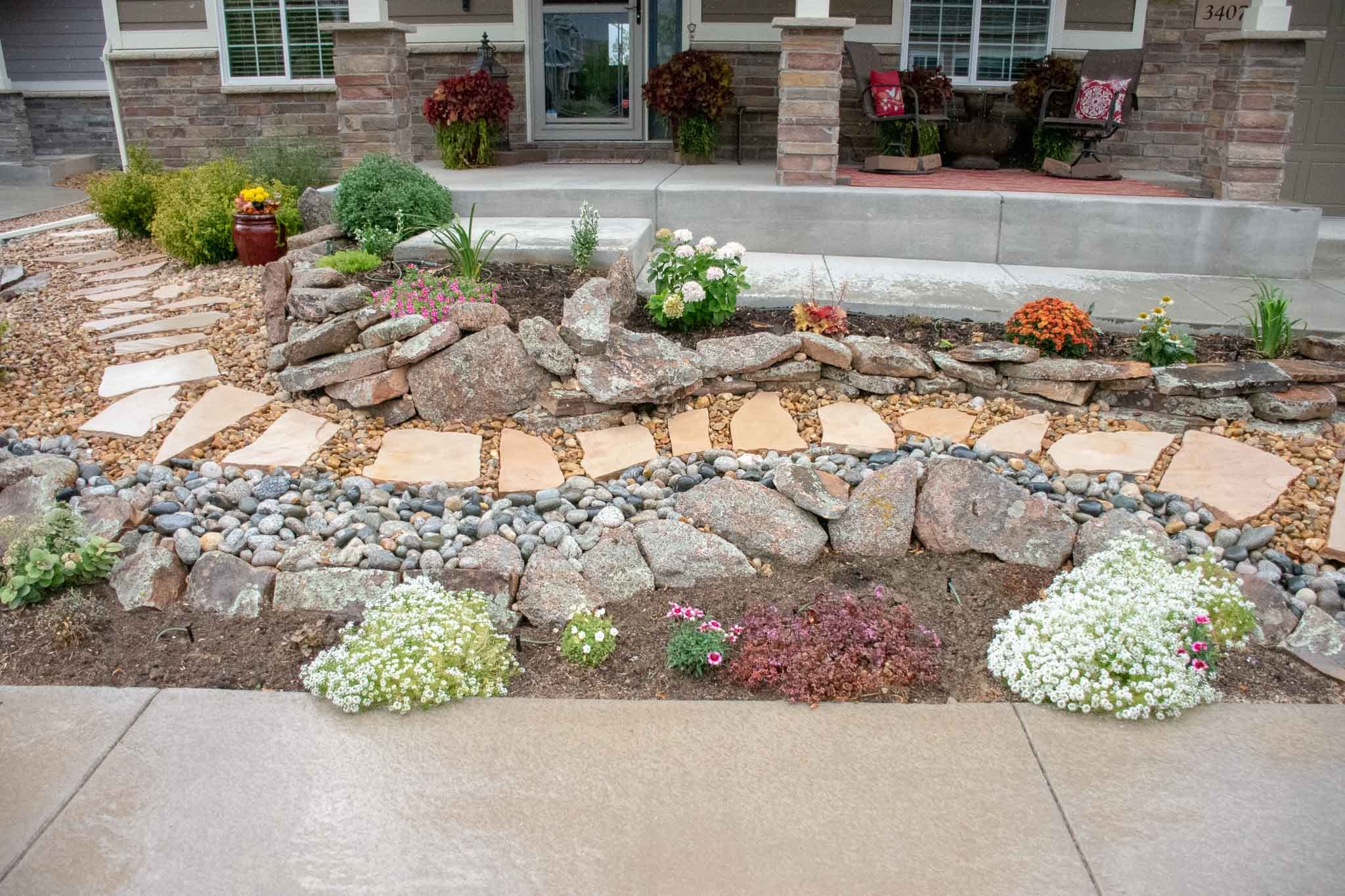 Front yard xeriscape that Tri City designed and completed in Loveland, CO 2019  Cobble stone dry river bed and flagstone pathway.