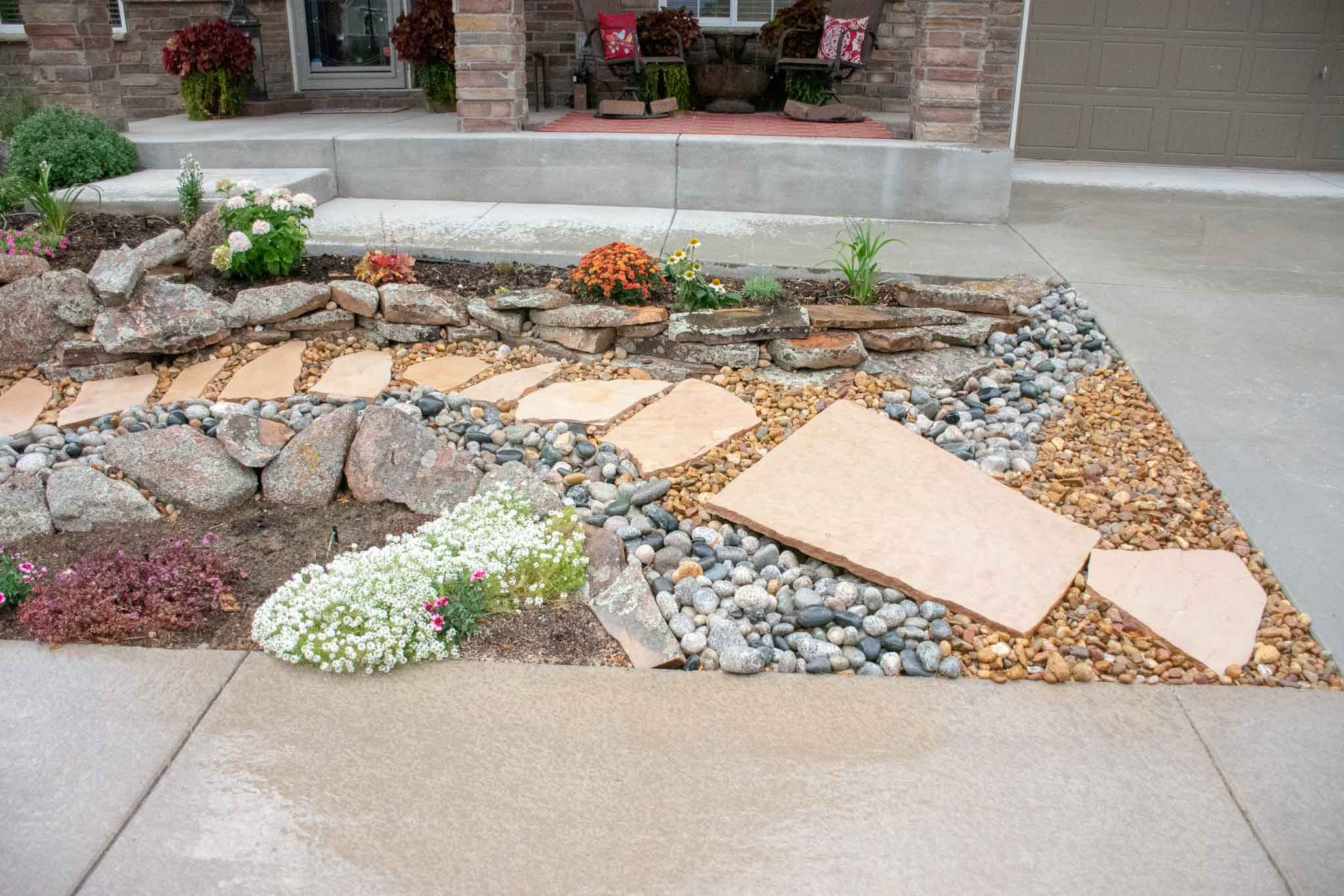 Front yard xeriscape that Tri City designed and completed in Loveland, CO 2019  Cobble stone dry river bed and flagstone bridge.