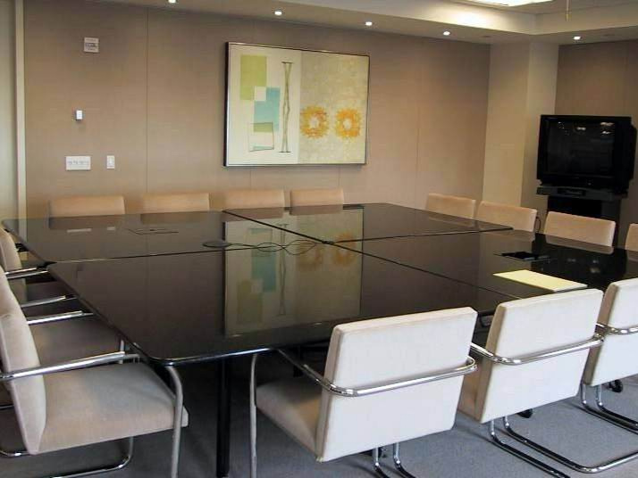 BAKER BOTTS - The walls in this conference room were painted a very bland color. By installing an artwork in the center of the wall, it broke up the uniformity and enlivened the space while keeping true to the soft shades of color prevalent throught the conference area.
