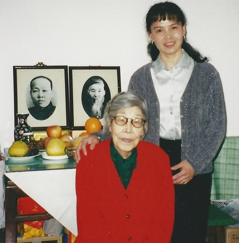 Grandmaster Cheng with her Sun style Tai Chi teacher, Sun Jianyun. The image to the right in the background is of Sun Jianyun's father, Sun Lutang, the founder of Sun style Tai Chi.