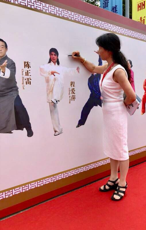 Grandmaster Cheng signing a picture of herself on the Wall of Fame at the 2018 World Tai Chi Cultural Festival in Sanya, China