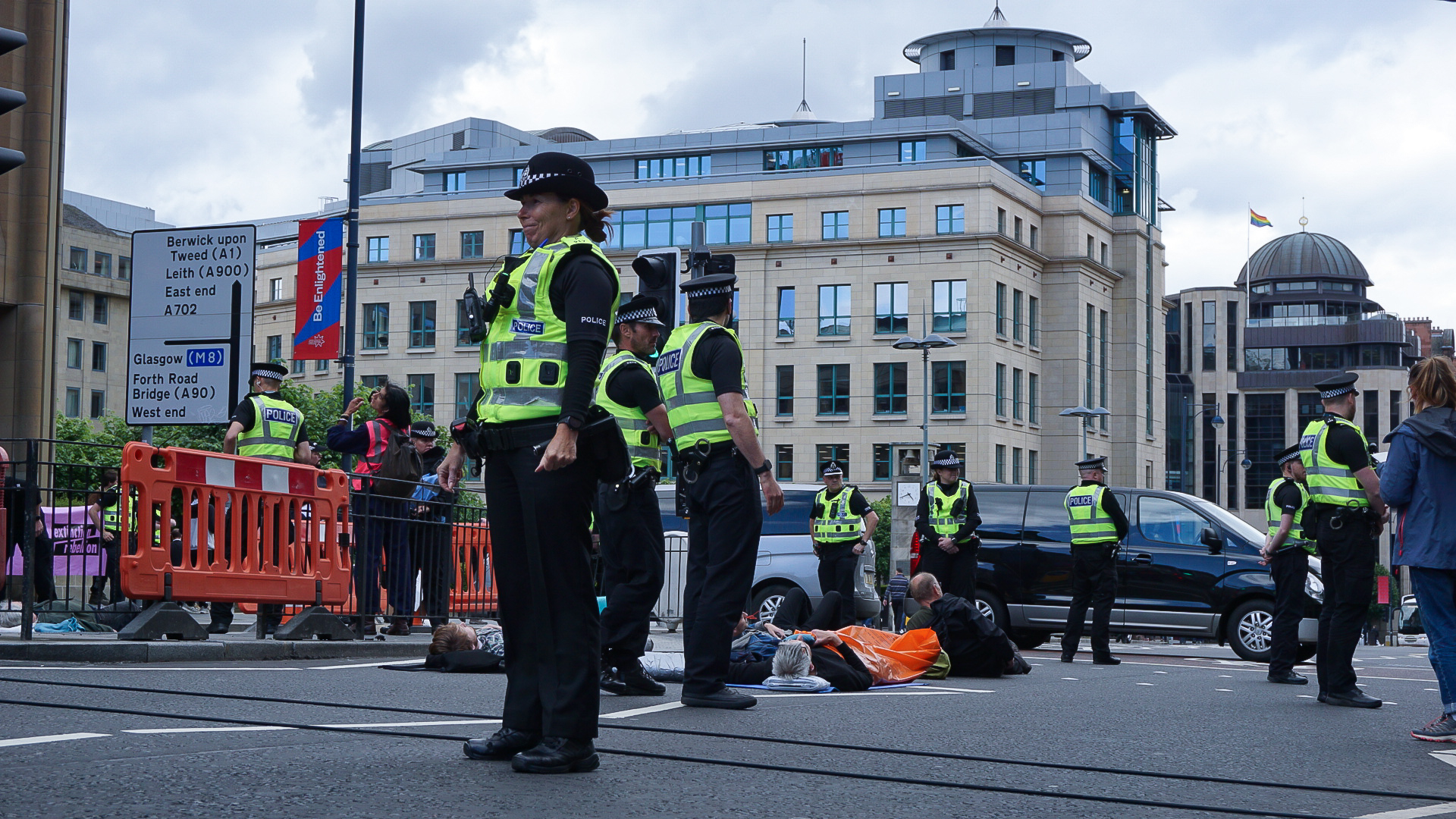 An alarming number of police surround activists who have laid down in the road.