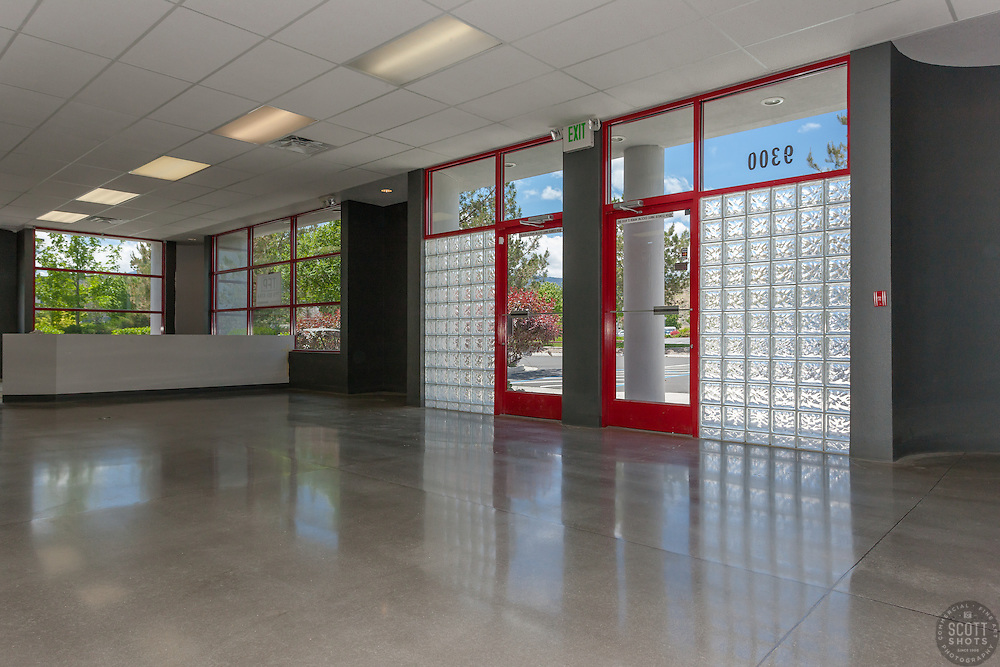 Commercial storefront in the daytime. View from the inside of polished concrete floor, natural light, and red accents on the door and windows.