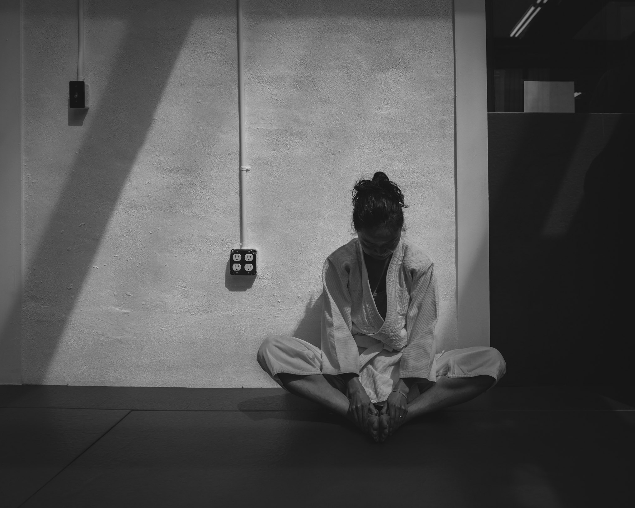 A beginning student stretches before an  Aikido class at Bushwick Dojo in Brooklyn, New York