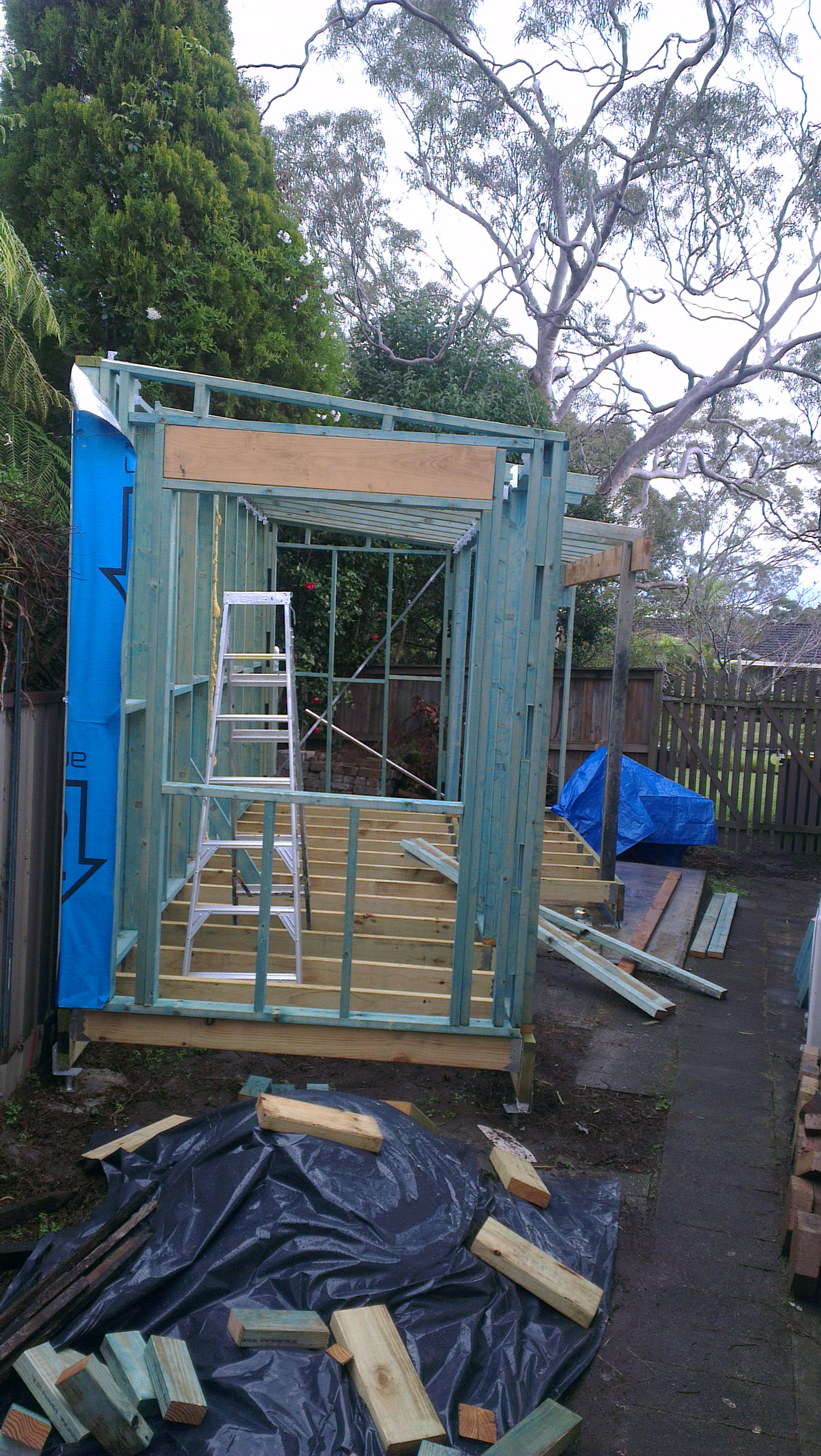 A shed being built, floor joists and wall supports can be seen with an aluminium ladder inside. More building materials are on the ground.