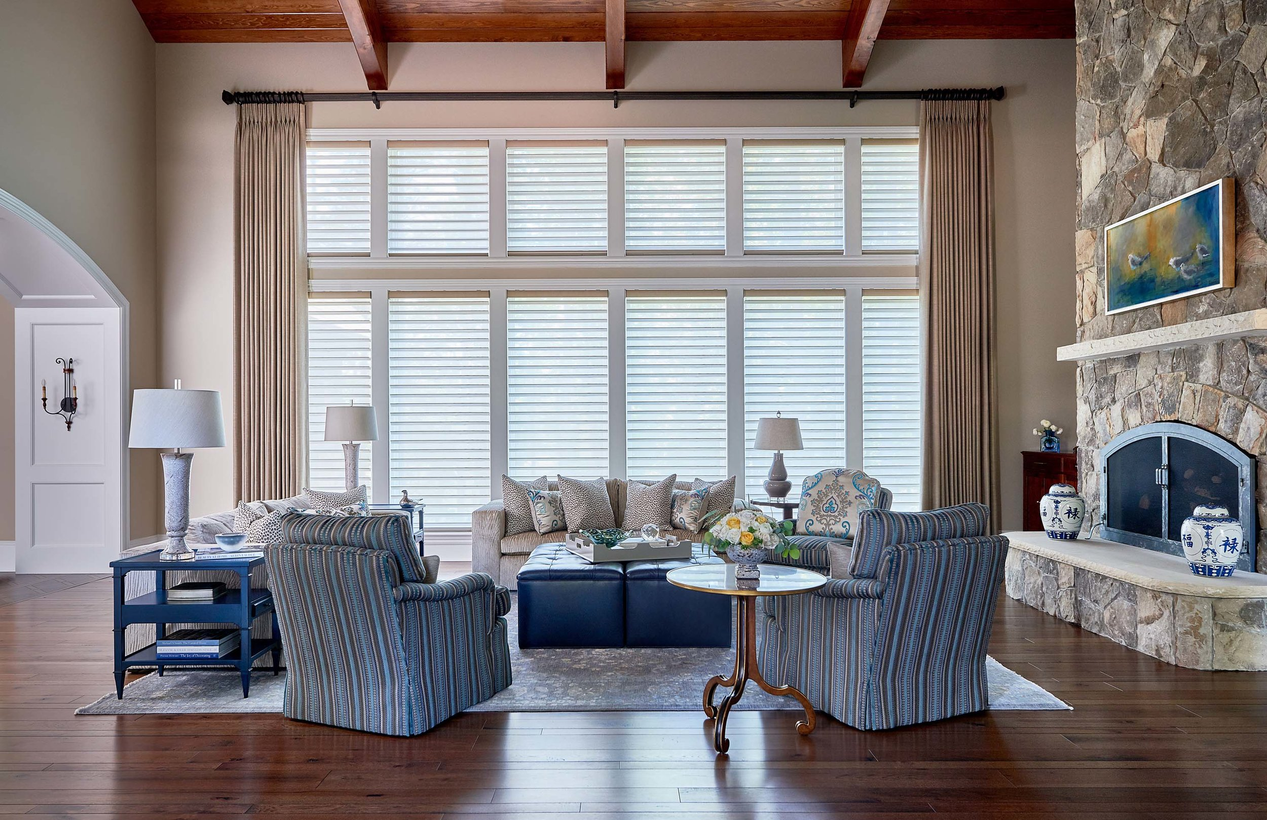 Grand living room - large window, blue and gray rug with neutral and blue upholstered sofa and chairs
