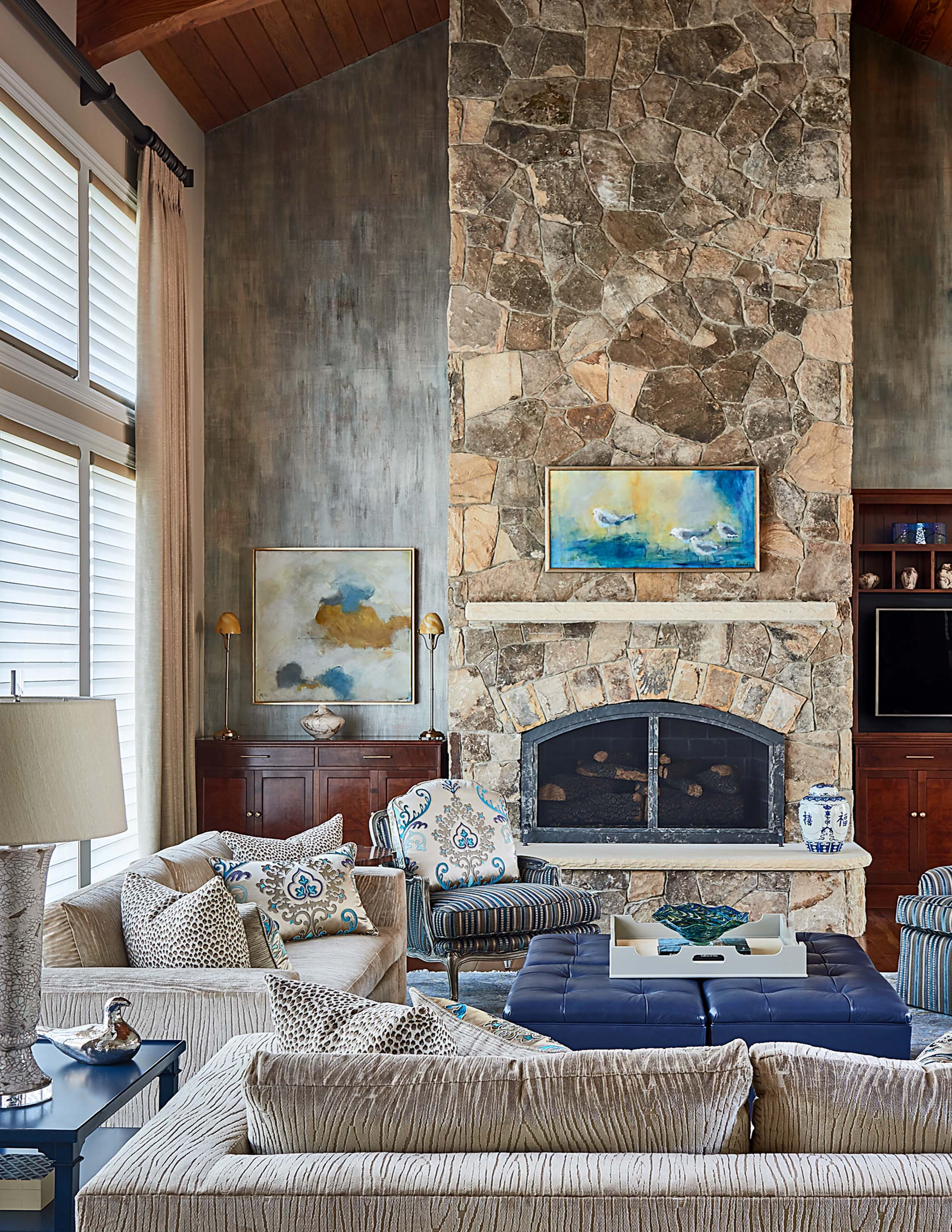 Two story living room with stone fireplace and walnut furniture
