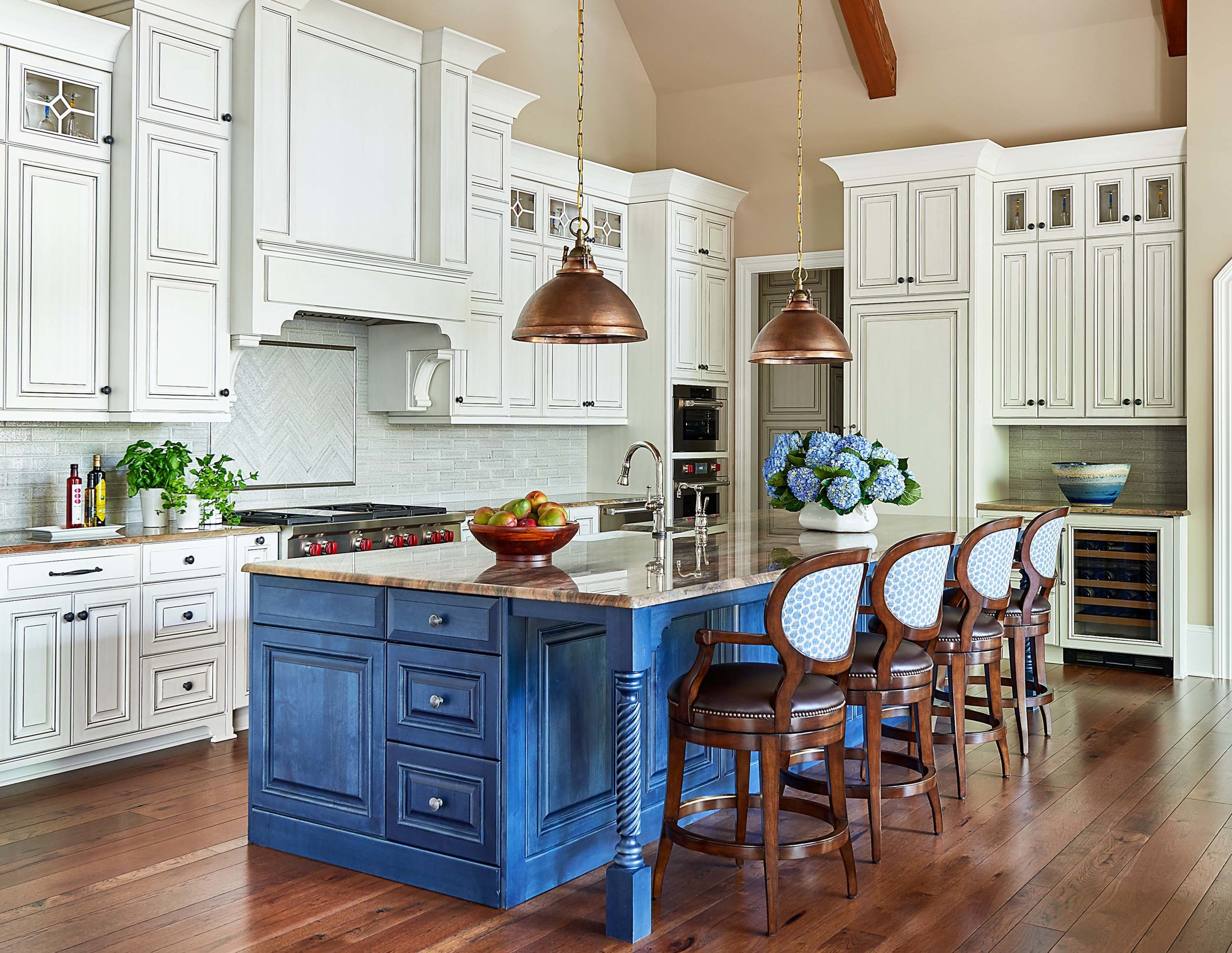 Luxury home kitchen with white cabinets and blue stained island with Currey and Company copper light pendants