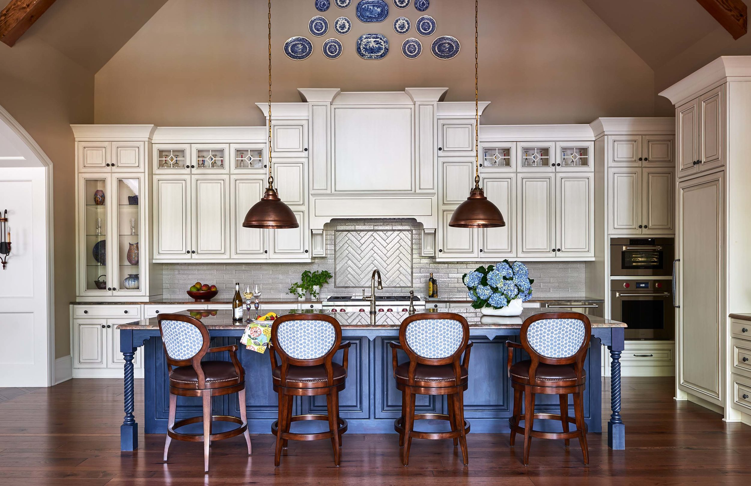 Off-white kitchen cabinets with blue island, copper pendants and blue and white transferware platter grouping on wall