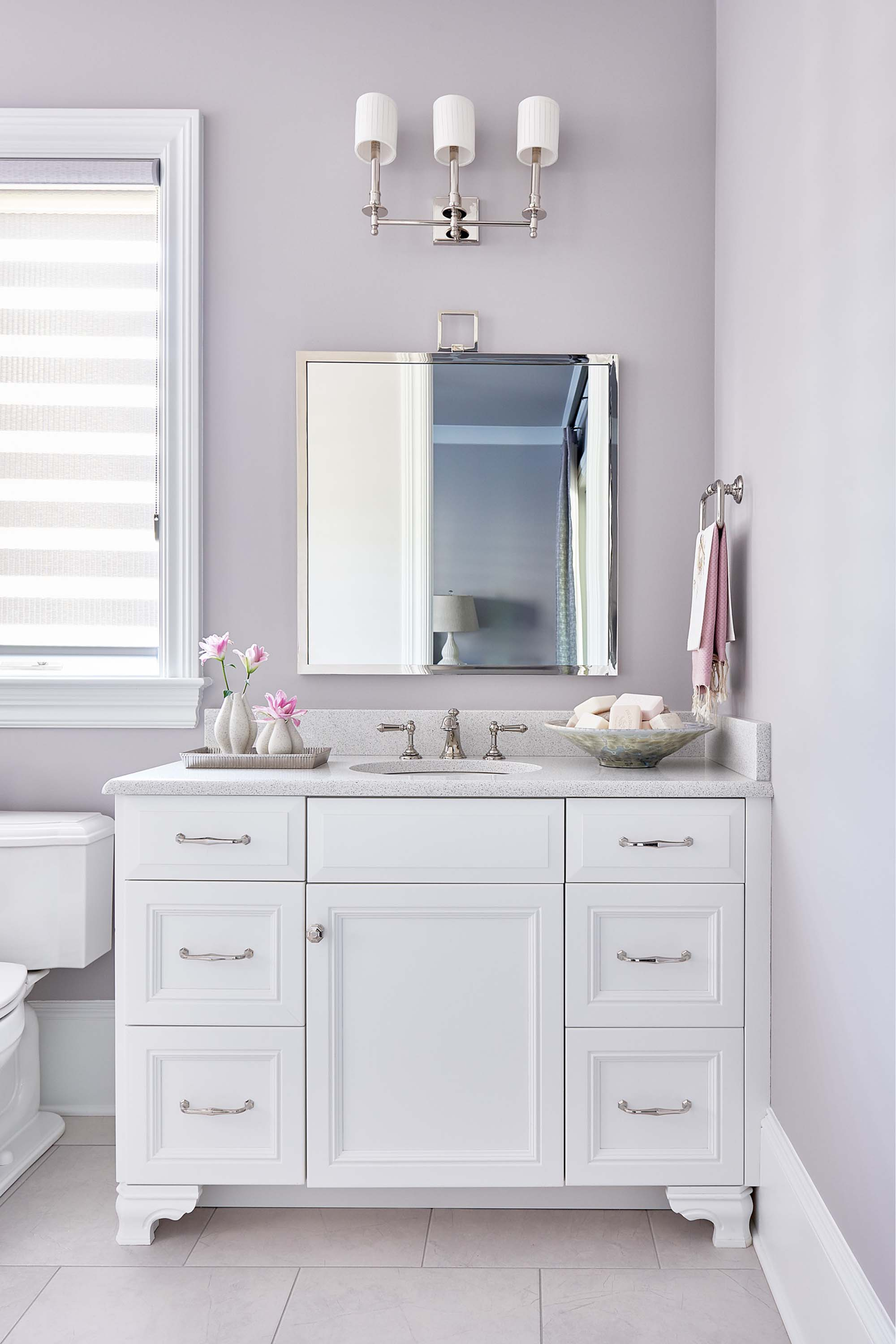 Guest bathroom with white vanity, lavender accent color