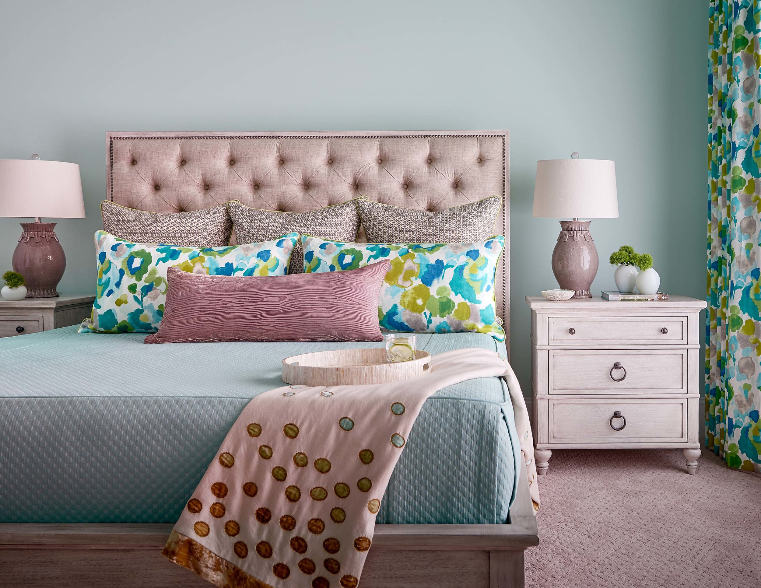 Guest bedroom with tufted headboard, aqua bedding and white-washed furniture, pottery lamps