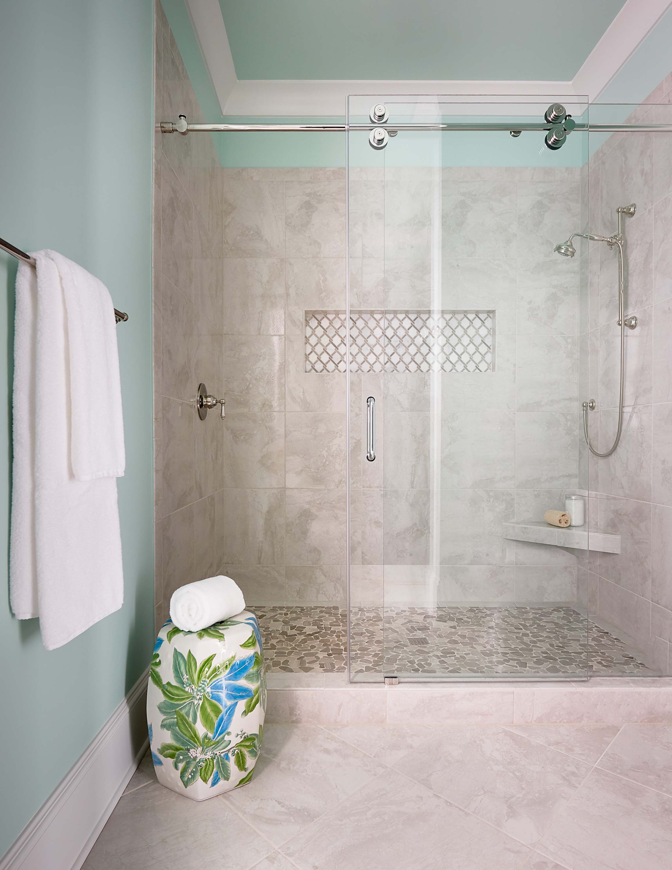 Guest bathroom with sliding glass shower door, neutral tile with aqua accents, garden seat