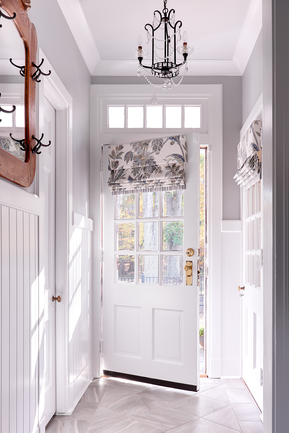 Mud entry to 1920's Cape Cod style home with tile floors and crystal chandelier and wainscoting on walls