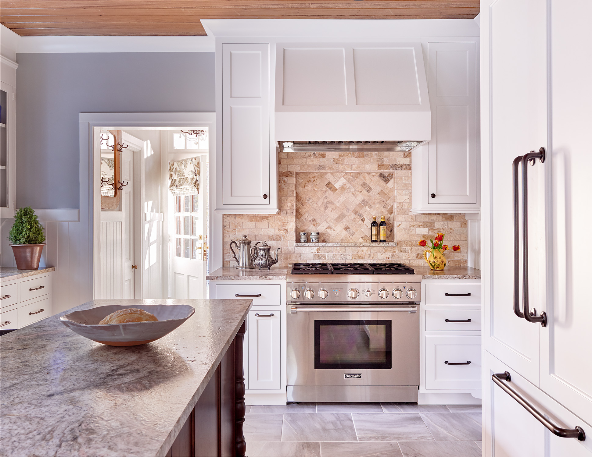Historic cottage home kitchen remodel with Thermador appliances and tumbled stone backsplash with natural stone counters