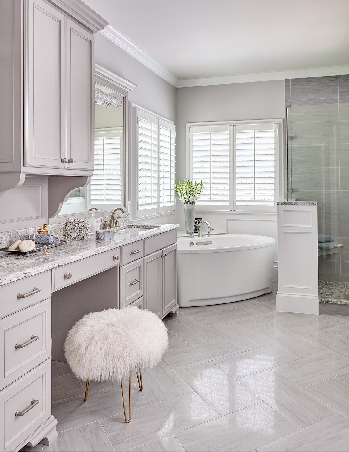 Master bathroom remodel with free-standing tub herringbone tile shutters on windows and custom cabinets with fluffy vanity stool