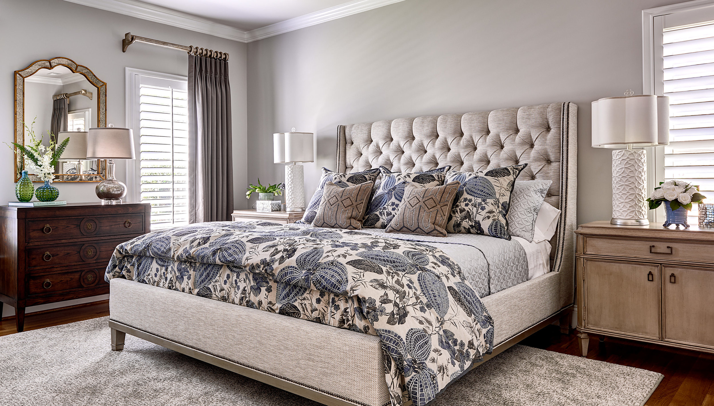Bedroom with tufted headboard on upholstered king-size bed with blue and gray leaf patterns on bedding and silk draperies