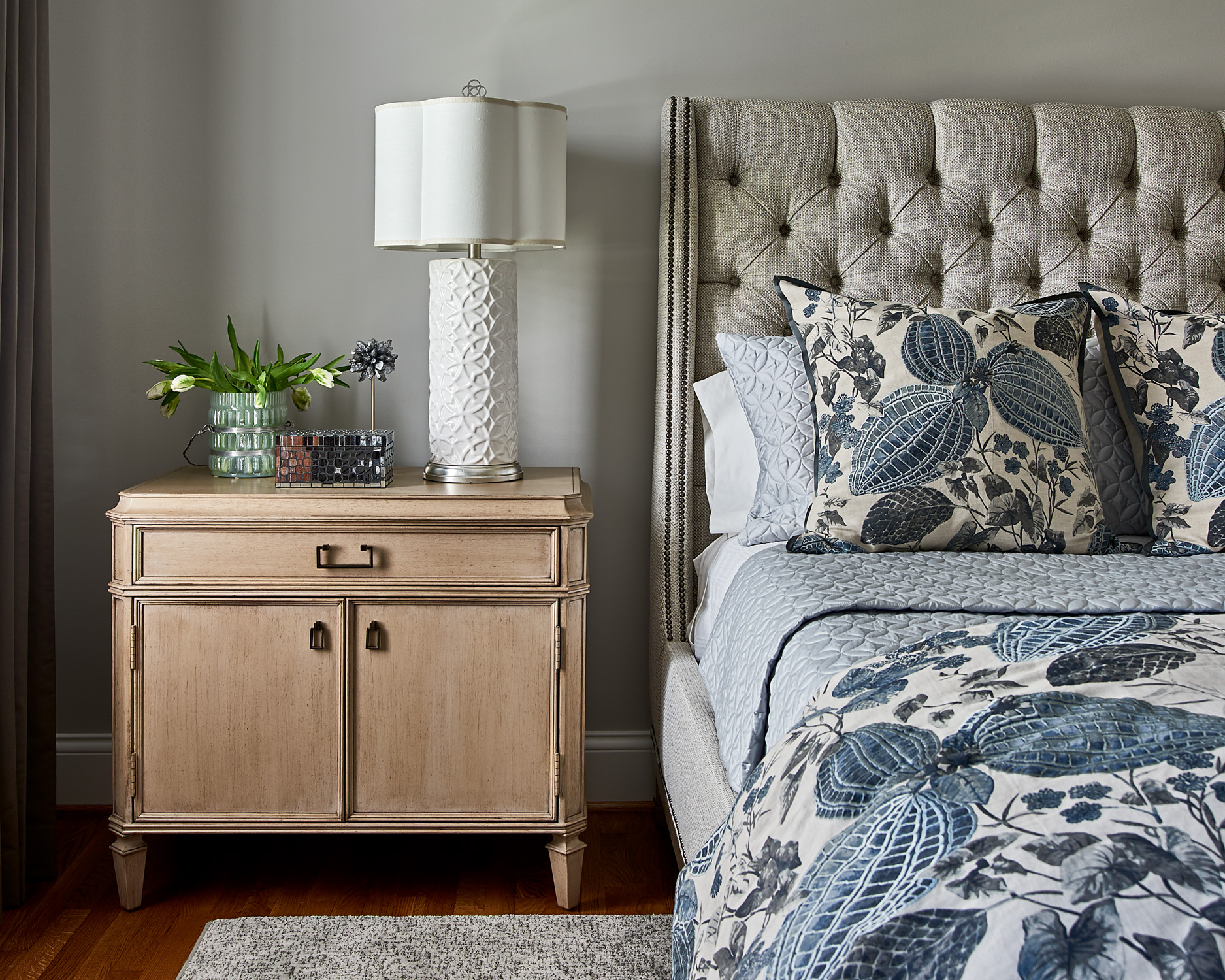 Bedroom with tufted bed and painted night table with scalloped lamp