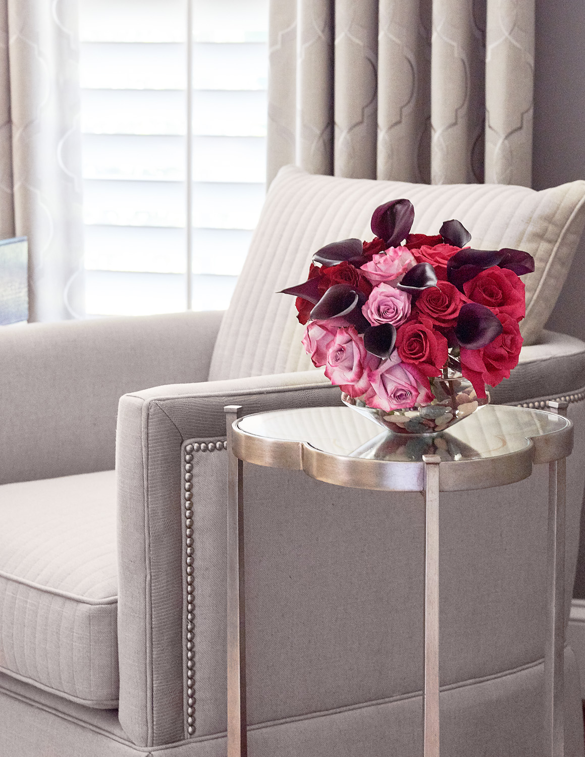 Swivel chair with mirrored top table with roses in living room
