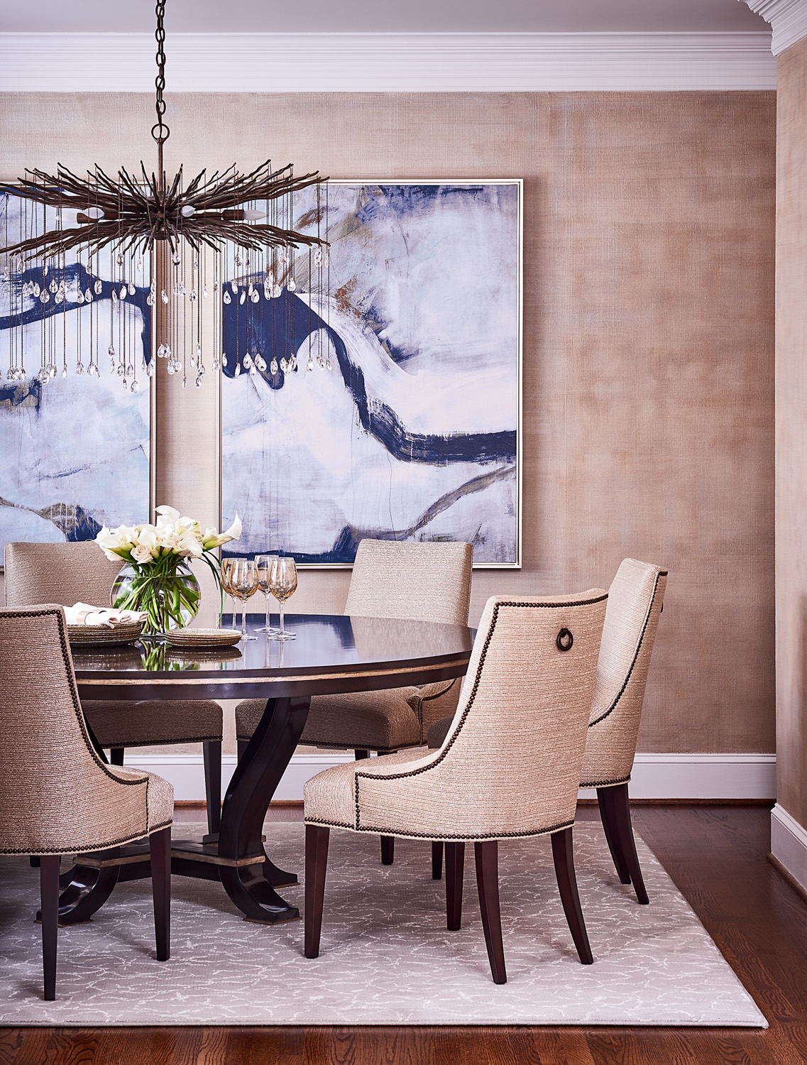 Transitional dining room with modern art in blue and round dining table with textured chairs with nailhead trim