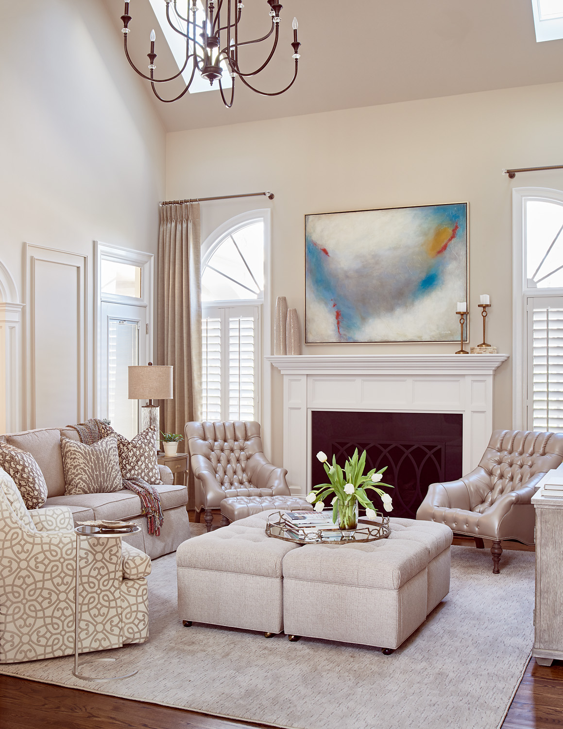 Neutral family room with sofa, chair, ottomans and tufted leather chairs fireplace with modern art and draperies