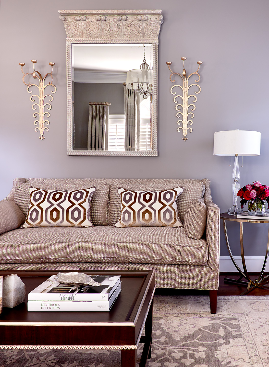 Living room with taupe modern sofa and cut velvet pillows and pediment mirror with scrolled sconces