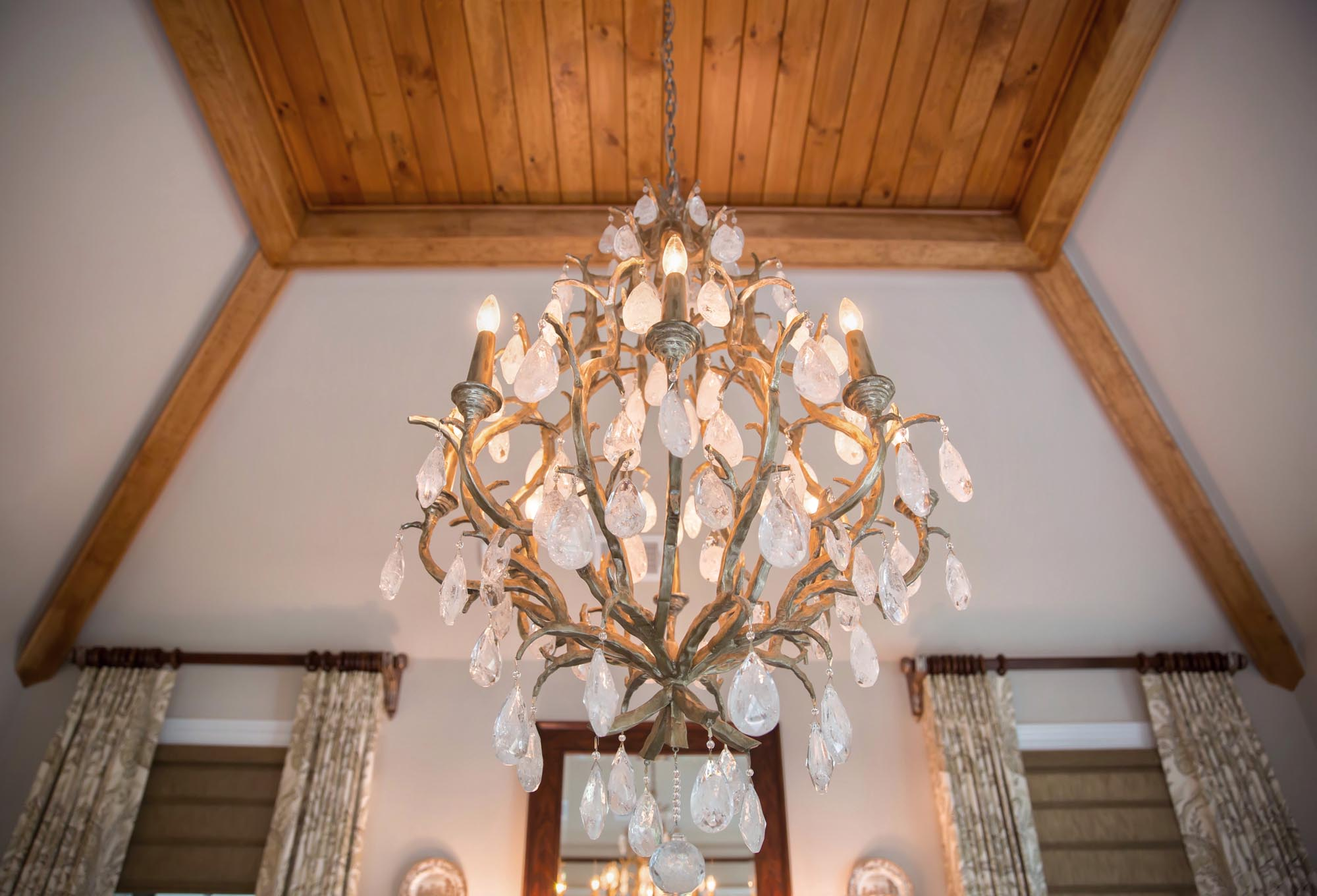 Rock crystal chandelier with planked wood ceiling in dining room