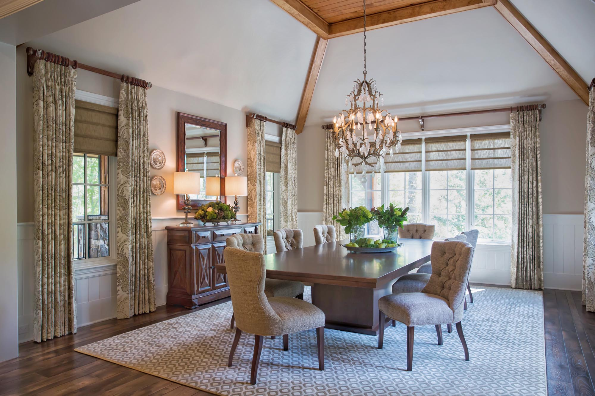 Casual elegant dining room with rock crystal chandelier modern dining table with tufted chairs and window treatments
