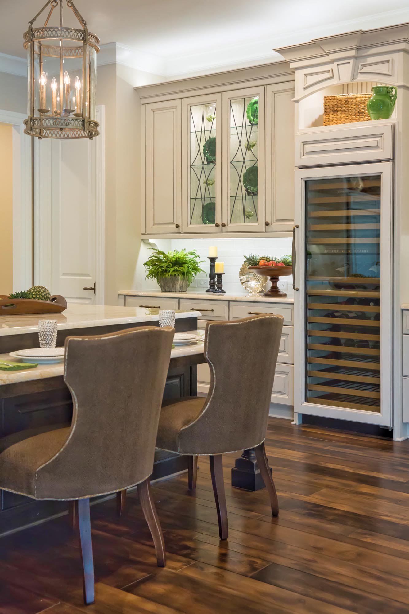 Cream traditional kitchen with counter chairs and wine refrigerator
