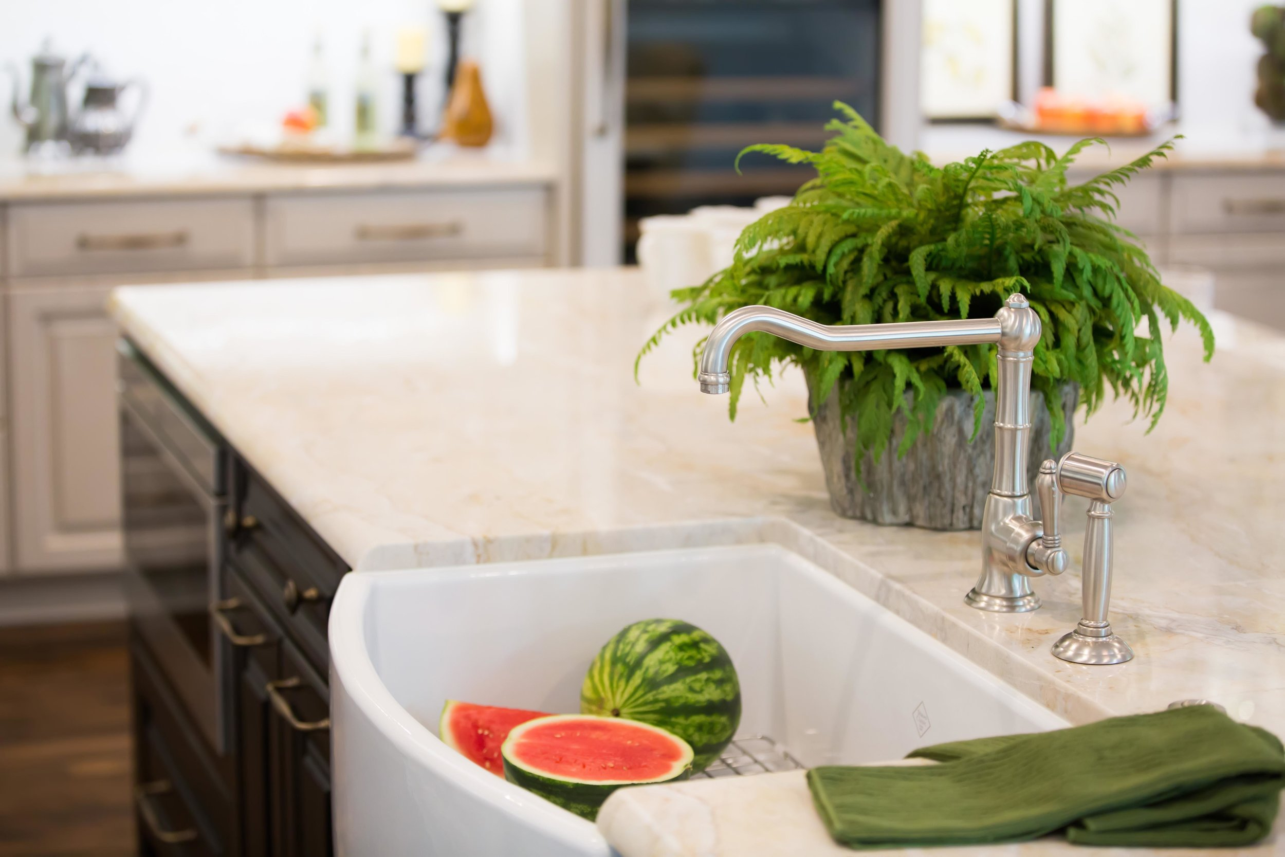 Farmhouse sink in kitchen island with quartzite counters