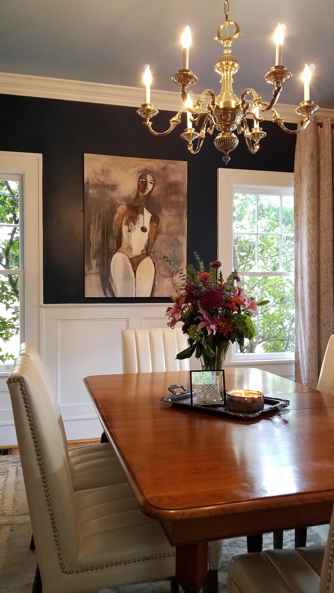 Dining room with wooden table, modern artwork on the wall and chandelier