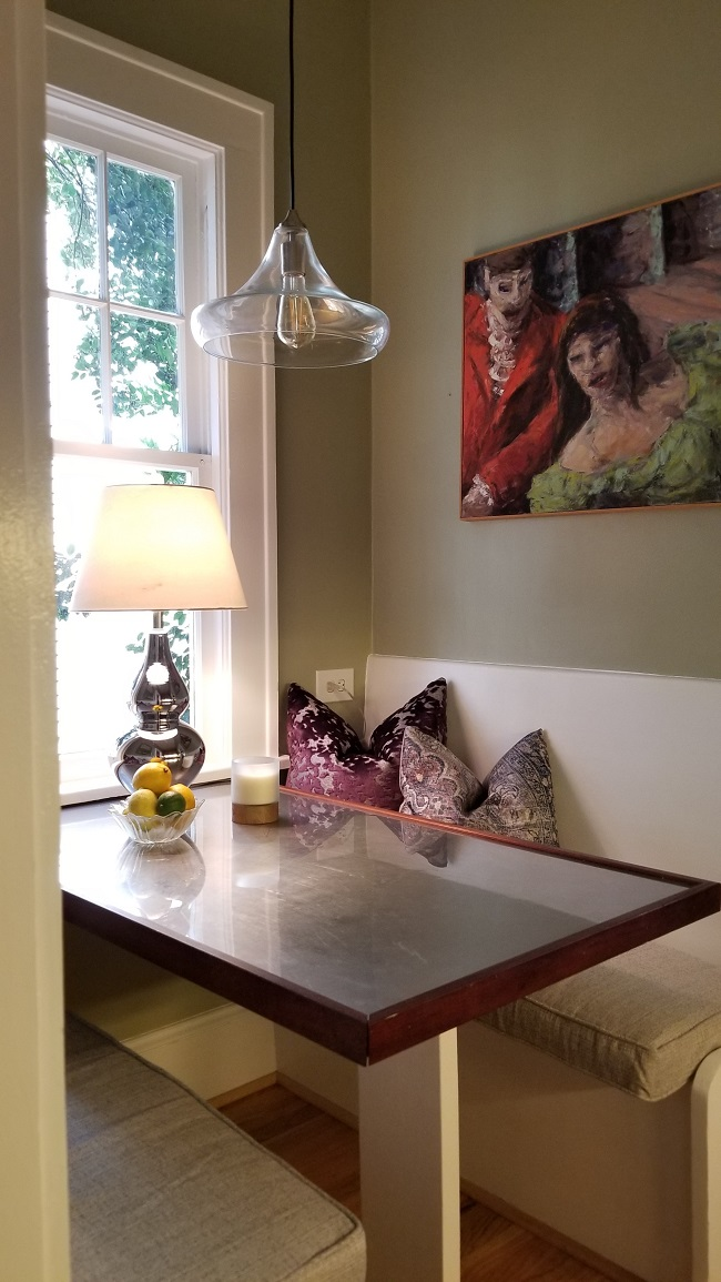 Dining table by the window with table lamp, pillows and artwork on the wall