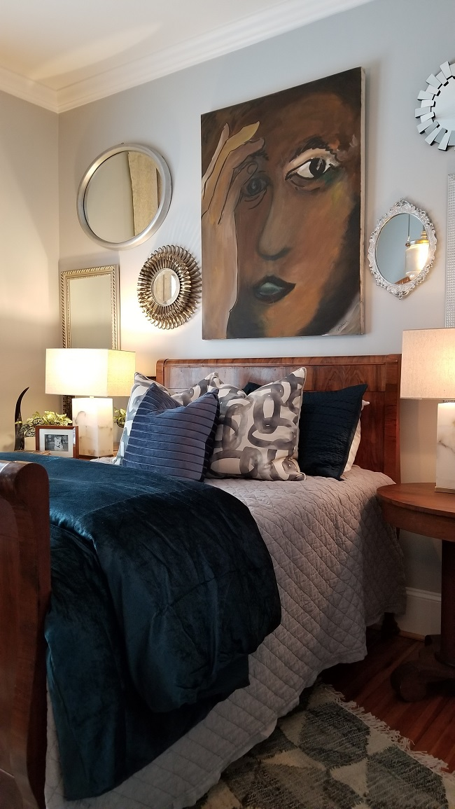 Bedroom with bed, set of pillows, bedside tables with table lamp and artwork on the wall
