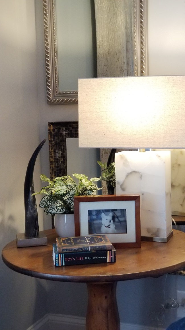 Bedside wooden round table with books, picture on frame and a table lamp