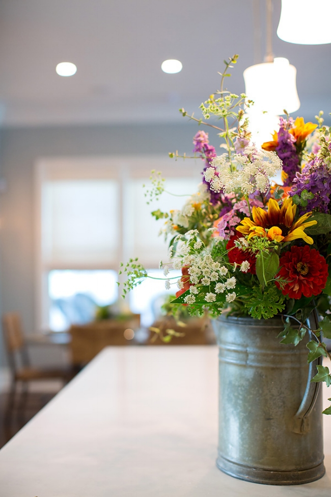 Elegance is in the eye of the beholder. A vintage watering can provided a lovely texture for the flowers arranged by August Lily Florist. (Sometimes we need professional assistance with home hugs!) Image: Wanda S. Horton Interior Design Photographer: Whitney Gray