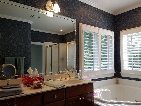 This is the 'before' of an owners' suite bath project. It had dark cabinets, a cultured marble vanity top, an old, jetted corner tub, white tile, a smaller shower, poor lighting, and the cabinet vanity design needed better function. The space felt chopped up and small.