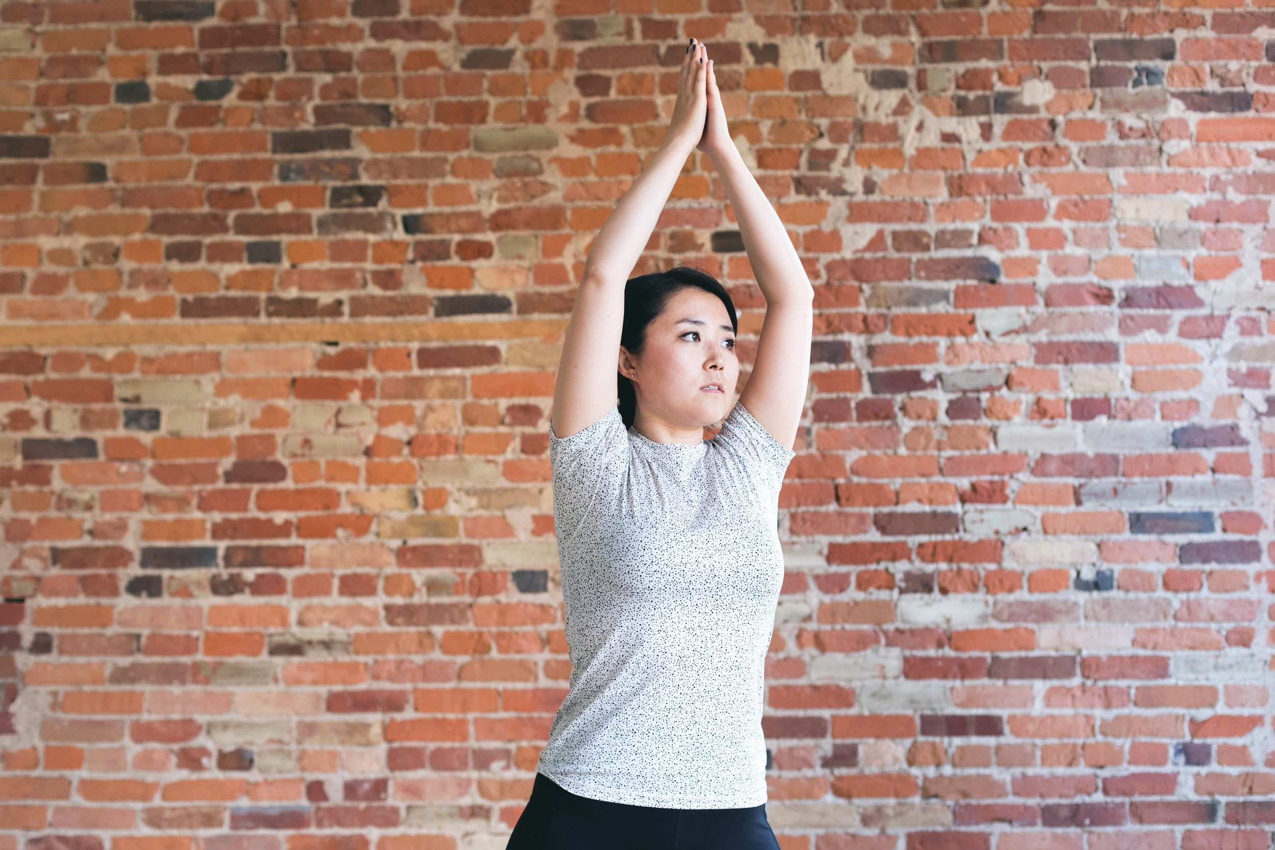 young-woman-against-exposed-brick-doing-yoga.jpg