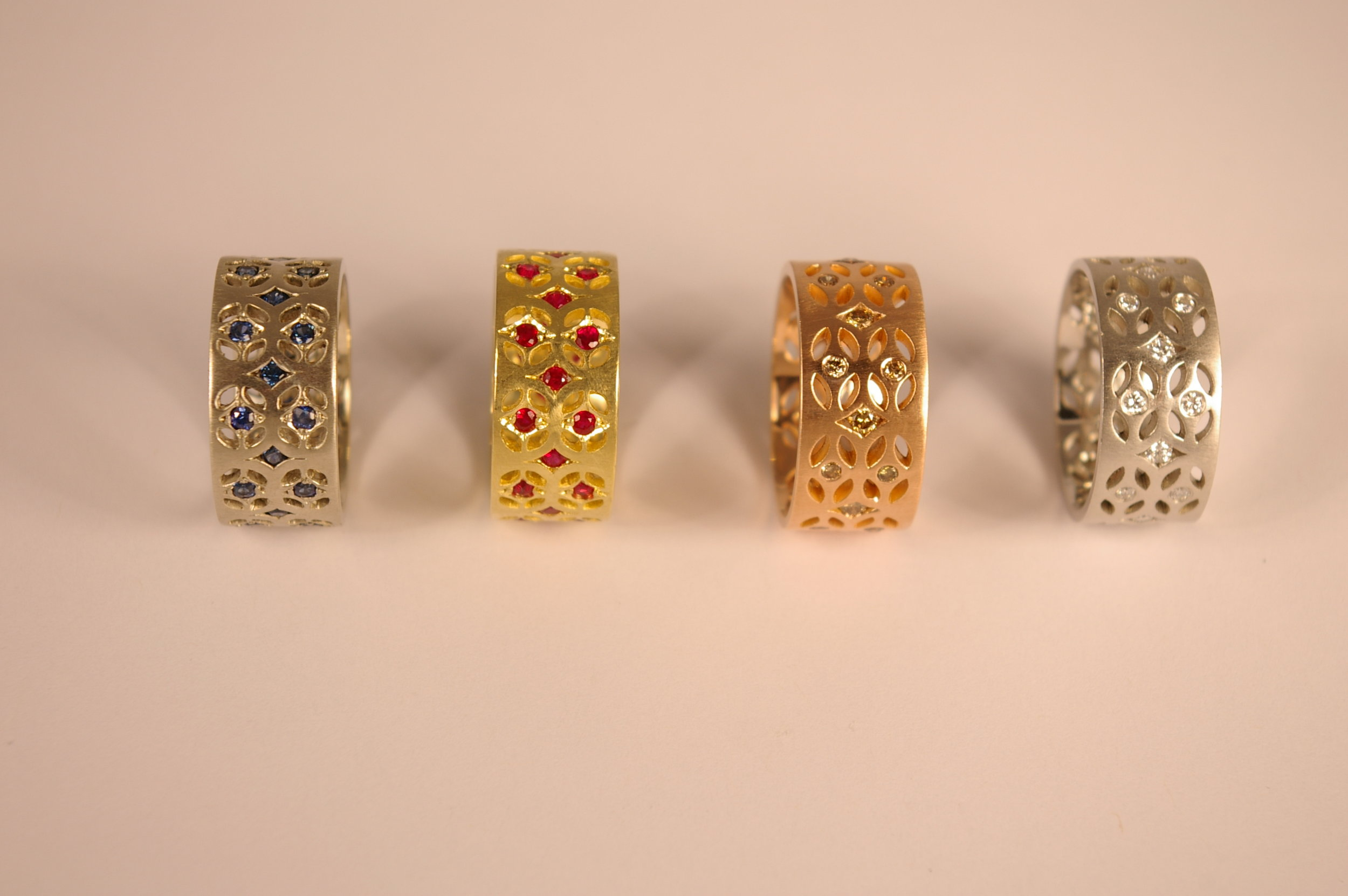 Set of 18 Karat Gold Bands, White Gold with Sapphires, Yellow Gold with Rubies, Rose Gold with Orange Diamonds, and Platinum with Diamonds (left to right)