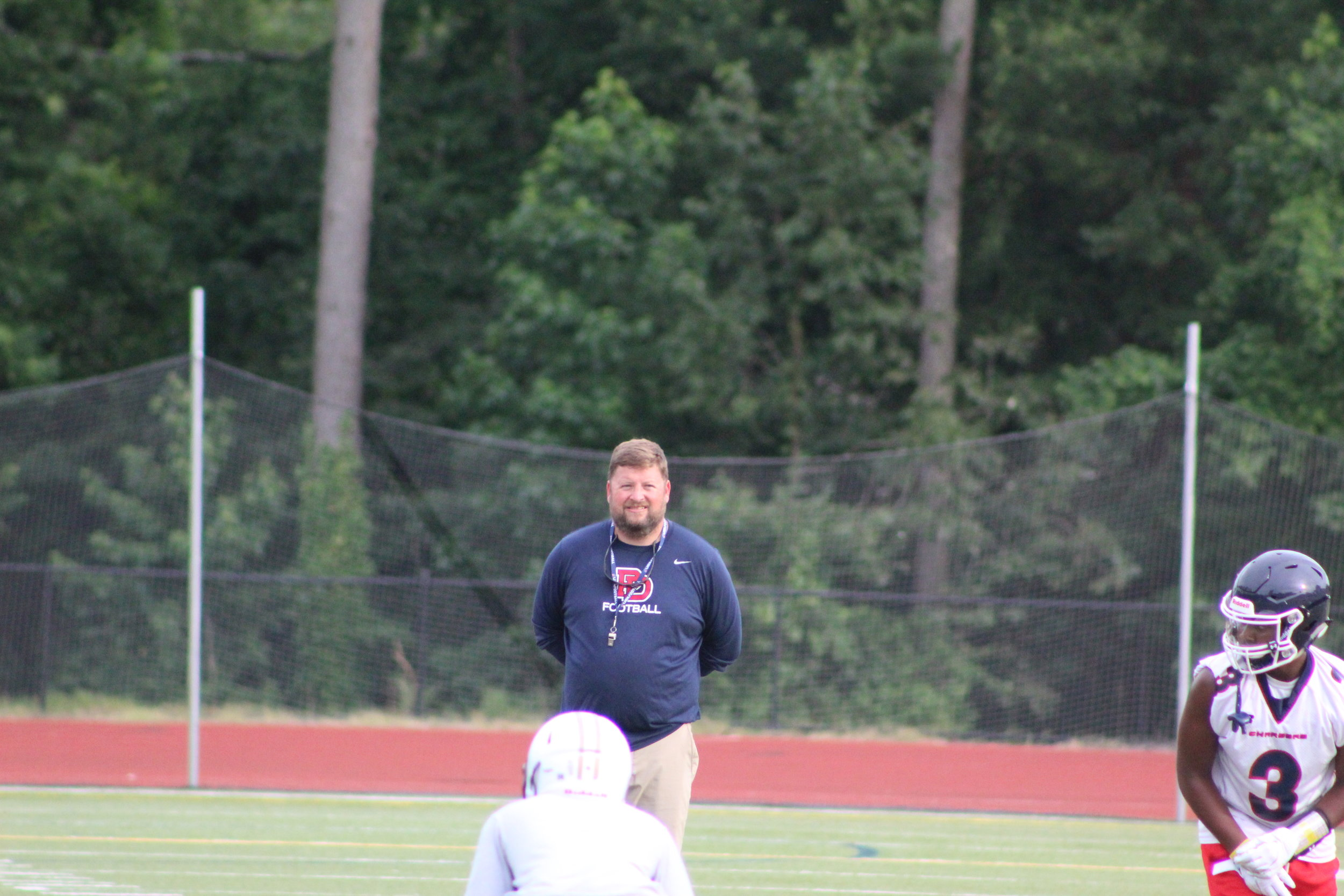 Providence Day Head Coach Adam Hastings overlooks his offense during a recent 7 on 7 scrimmage