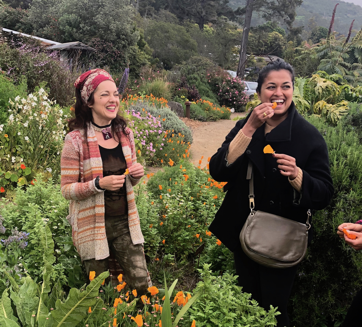 Shankari teaching class on edible flowers at Esalen Institute while student tastes a flower