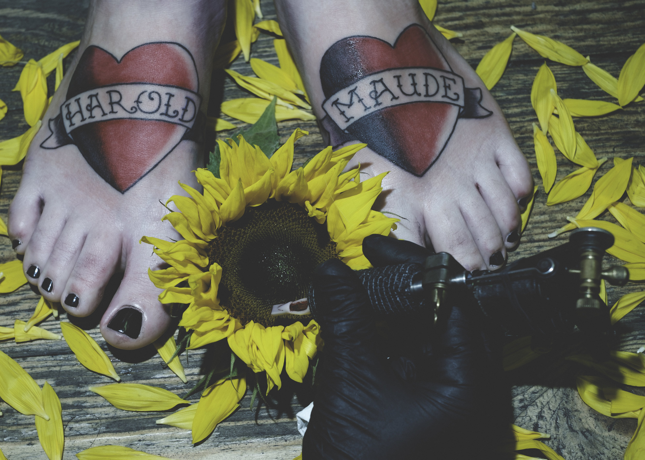 Alex Simpson tattooing Lucy's feet, captured by Adam J. Pegg.