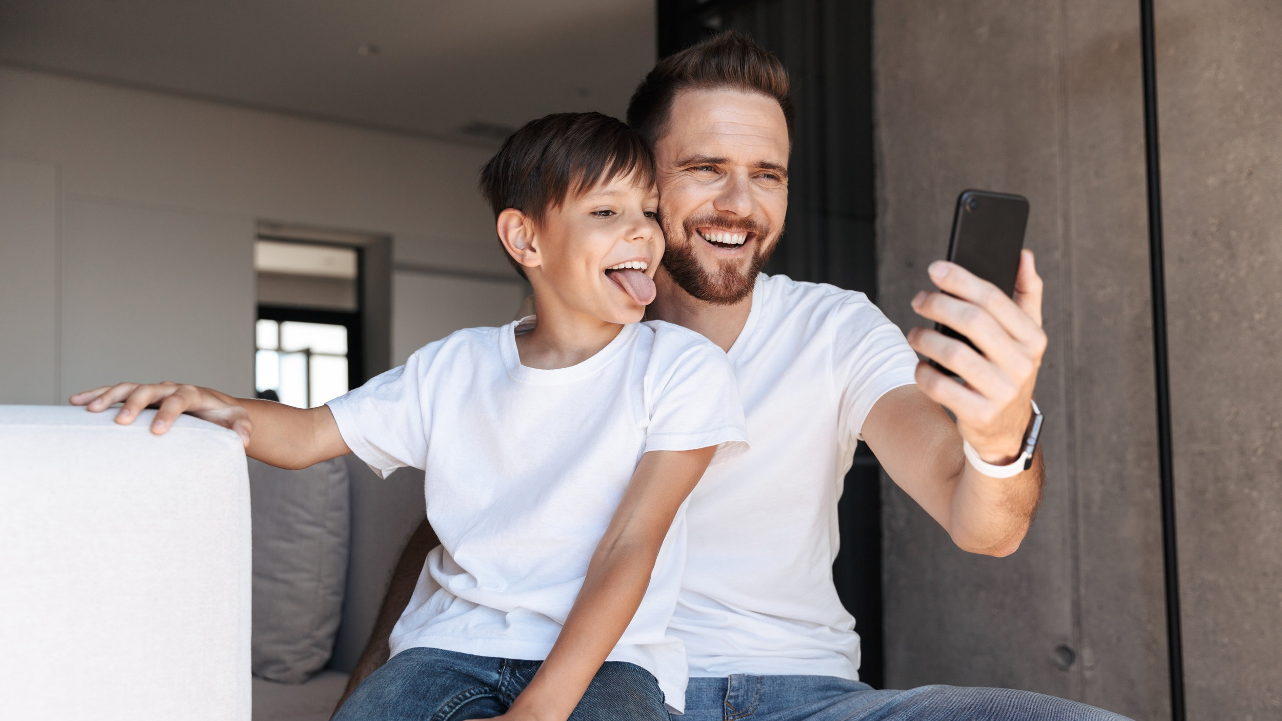 cheerful-young-man-father-dad-using-mobile-phone-2NQM7HD.jpg