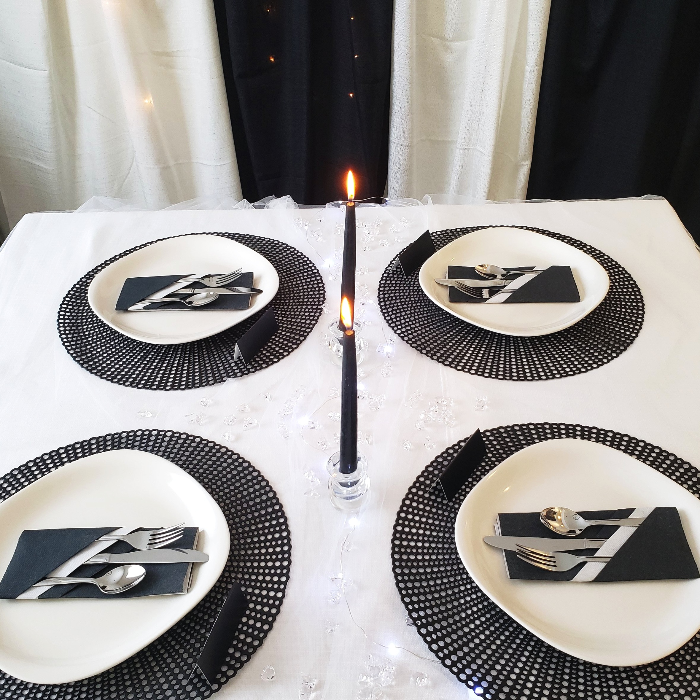 Classic Black & White Table - Black and white table setting. We used a white table cloth topped with white sheer. Added some small clear stones, glass candle holders and black candles. Finished it off with black place mats, black place cards, white plates and cool folded napkins.