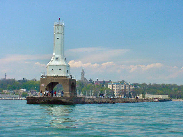A view of the art-deco style lighthouse and breakwater bordering the Port Washington Harbor