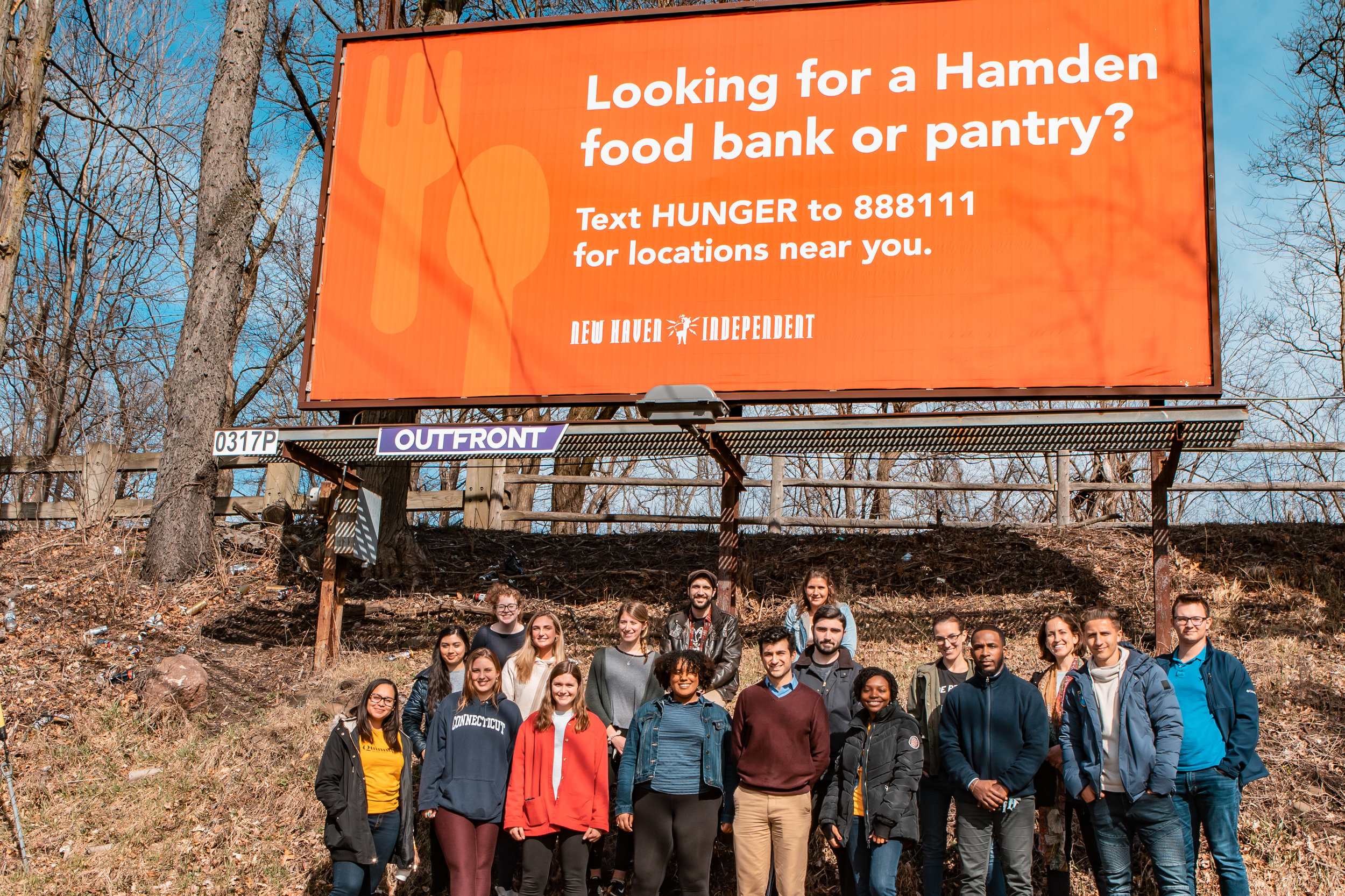 Students and professors pose in front of one of the billboards on Dixwell Avenue.