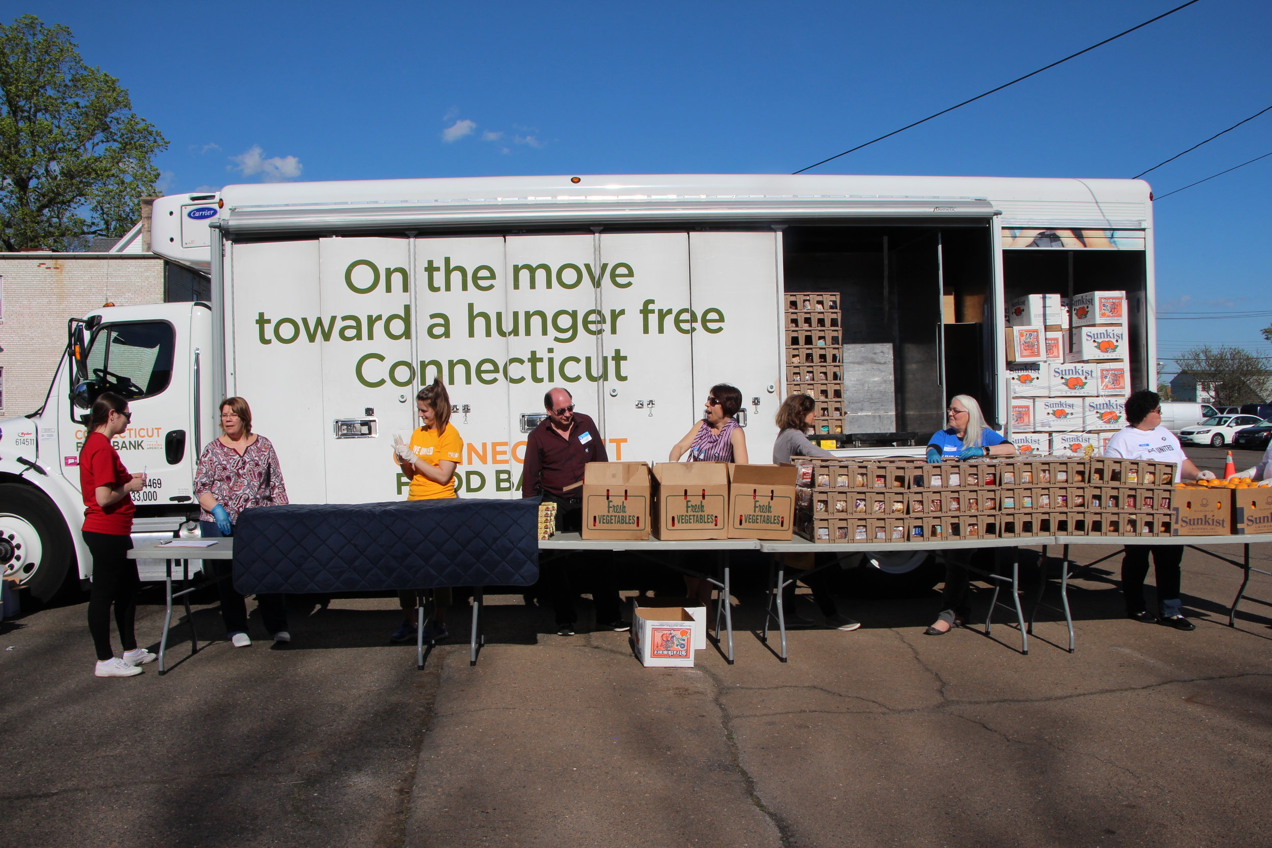 Volunteers set up in front of the Connecticut Food Bank's mobile food pantry truck in The Christ the Bread of Life Parish parking lot.