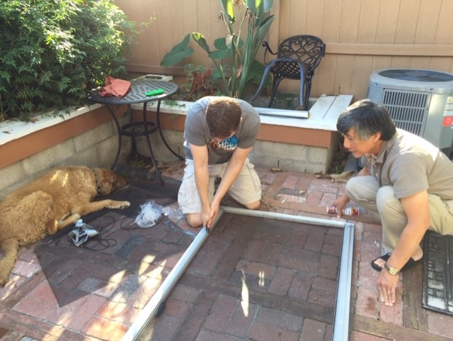 Elijah and my dad (and Dasher the dog!) repair the backdoor screen.